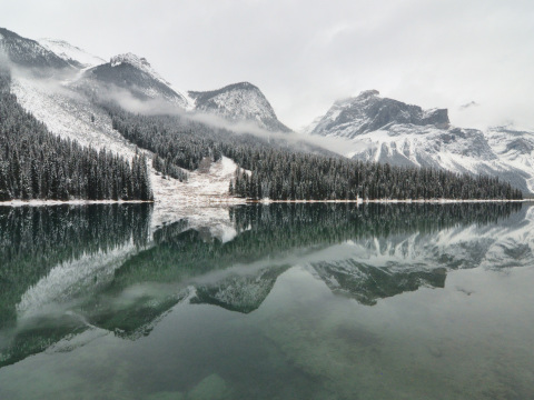 The snow touched mountains and trees surrounding Emerald Lake in Alberta are reflected in the ice cold water.