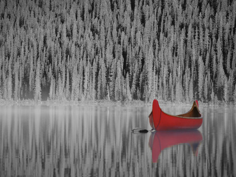 A large canoe sits on a calm lake, the trees behind it reflecting in the calm water.