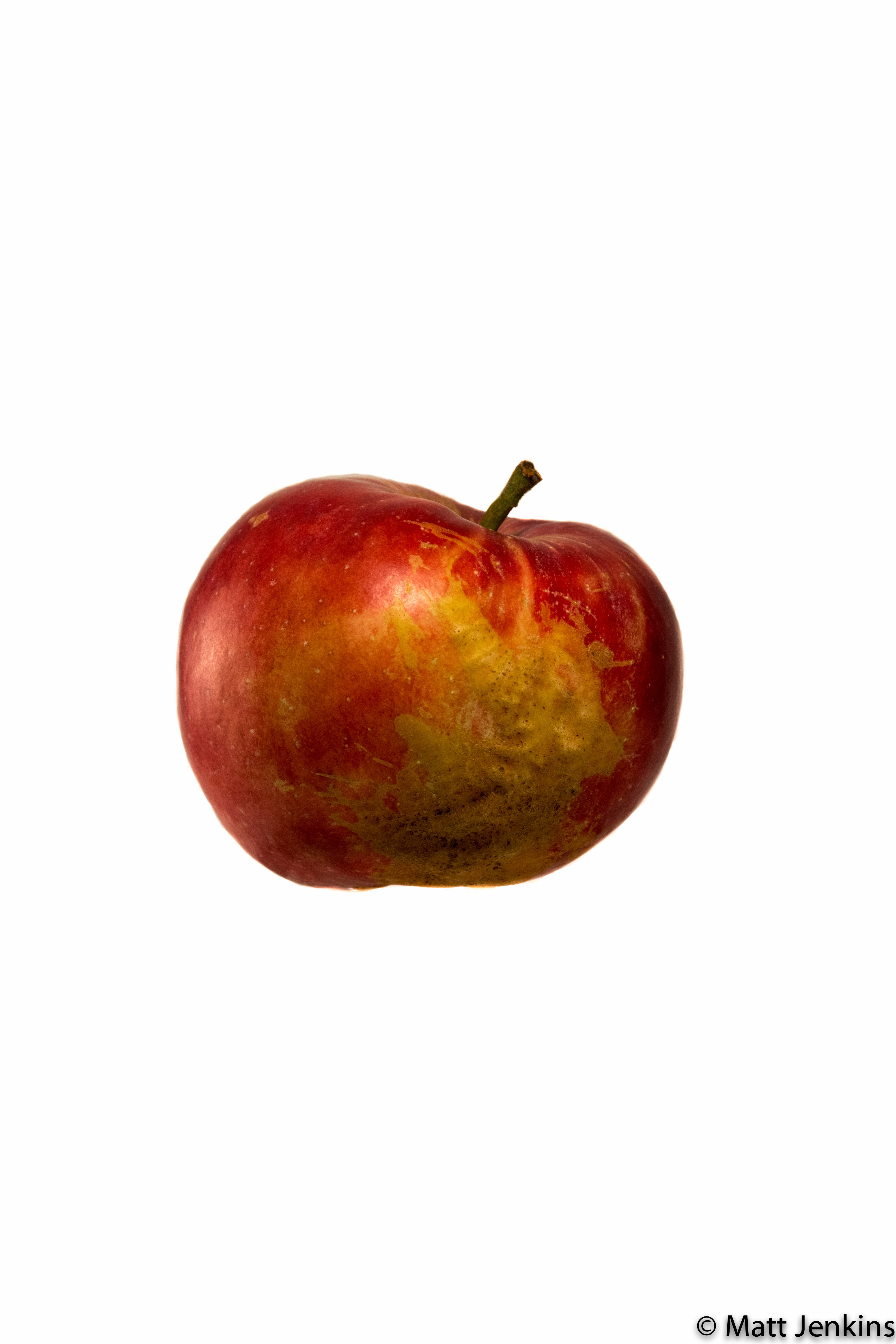A aesthetically flawed apple on white background